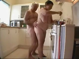 Grandmother and old man having enjoyment in the kitchen